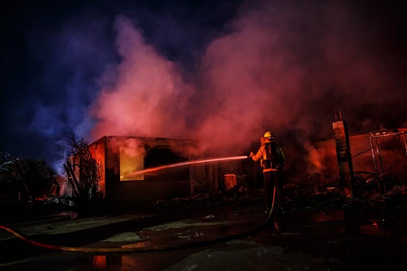 Firefighters mop up wreckage of a home destroyed by the Hillside fire Oct. 31 in San Bernardino.