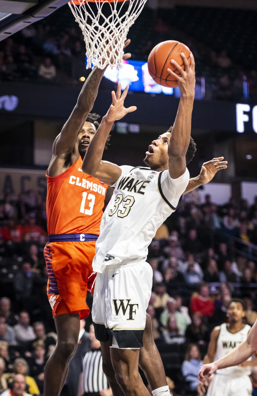 Wake Forest forward Ody Oguama (33) shoots next to Clemson guard Tevin Mack (13) during an NCAA college basketball game Saturday, Feb. 1, 2020, in Winston-Salem, N.C. (Andrew Dye/The Winston-Salem Journal via AP)