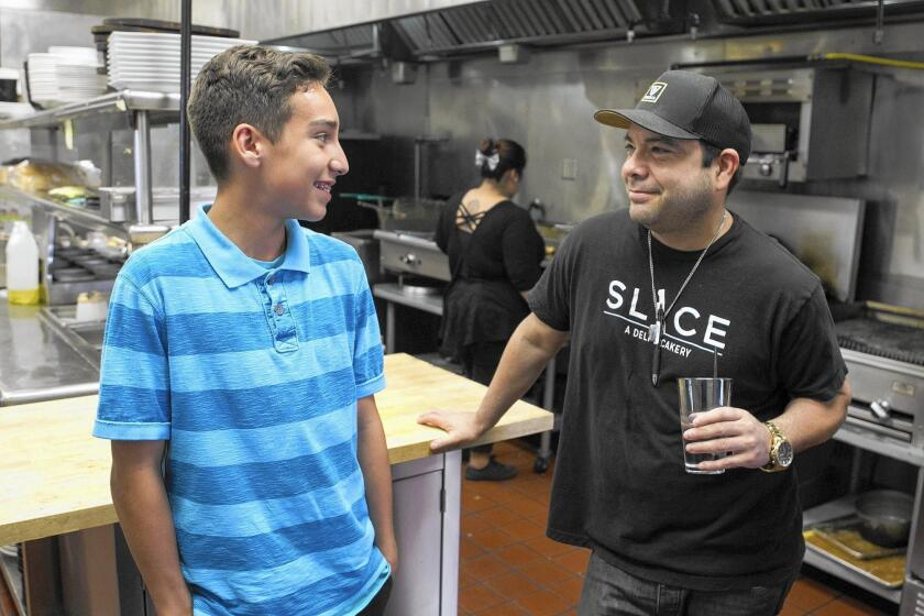 Ethan Sanchez, left, 13, works with his father John at his restaurant Slice Deli and Cakery in Fountain Valley.