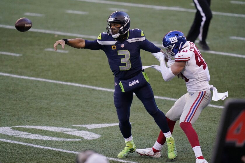 Seattle Seahawks quarterback Russell Wilson (3) passes under pressure from New York Giants linebacker Carter Coughlin (49) during the second half of an NFL football game, Sunday, Dec. 6, 2020, in Seattle. The Giants won 17-12. (AP Photo/Elaine Thompson)