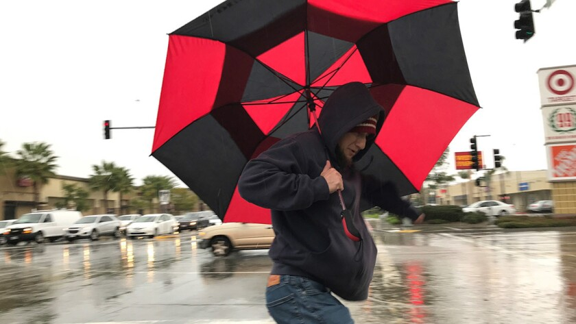 A pedestrain crosses an intersection in Clairemont during a midday down pour Monday. K.C. Alfred