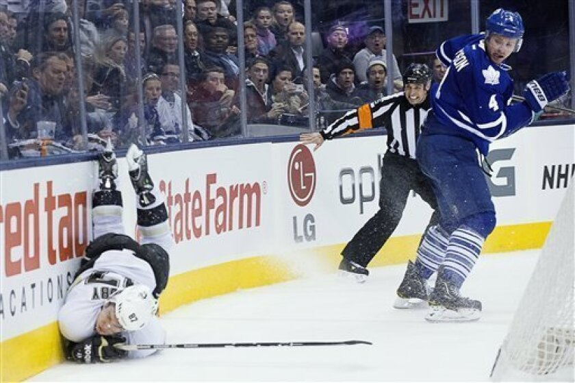 Pittsburgh Penguins' Sidney Crosby, left, collides with the boards as Toronto Maple Leafs' Cody Franson looks back during third period NHL hockey action in Toronto on Saturday, March 9, 2013. (AP Photo/The Canadian Press, Chris Young)