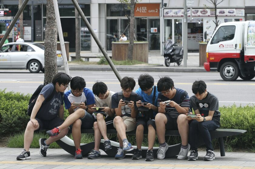 FILE - In this July 16, 2015, file photo, South Korean high school students play games on their smartphones on a bench on the sidewalk in Seoul, South Korea. Security researchers say they found critical weaknesses in a South Korean government-mandated child surveillance app, vulnerabilities that could have allowed hackers to easily violate the private lives of the country's youngest citizens. (AP Photo/Ahn Young-joon, File)