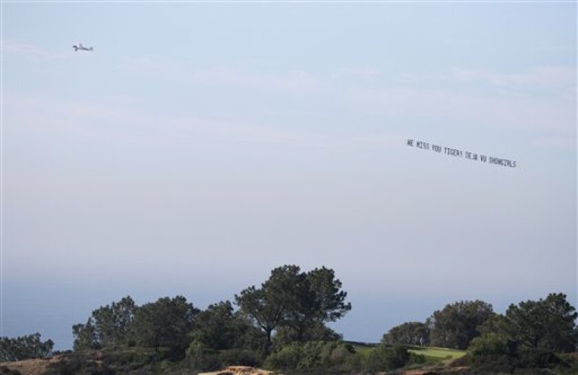 An airplane pulls a banner over the Torrey Pines golf course with a message from a local strip club for Tiger Woods during the opening round of the Farmers Insurance Open golf tournament at Torrey Pines Thursday Jan. 28, 2010 in San Diego. (AP Photo/Chris Park)