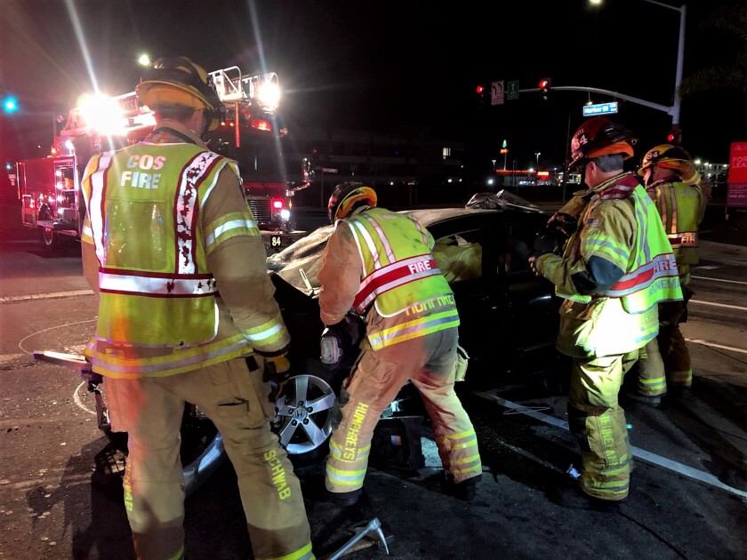 Firefighters extricate a man from his vehicle near Harbor Boulevard and South Coast Drive.