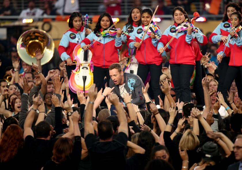 Chris Martin de Coldplay canta con YOLA tocando atrás.