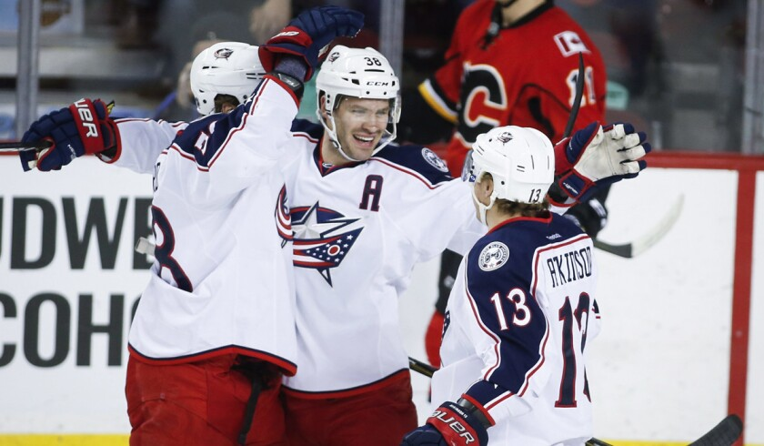 Columbus Blue Jackets' Boone Jenner, center, celebrates his goal with teammates David Savard, left, and Cam Atkinson during the first period against the Calgary Flames on Friday.