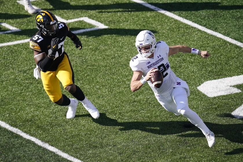 Northwestern quarterback Peyton Ramsey runs from Iowa defensive lineman Chauncey Golston (57) during the first half of an NCAA college football game, Saturday, Oct. 31, 2020, in Iowa City, Iowa. (AP Photo/Charlie Neibergall)