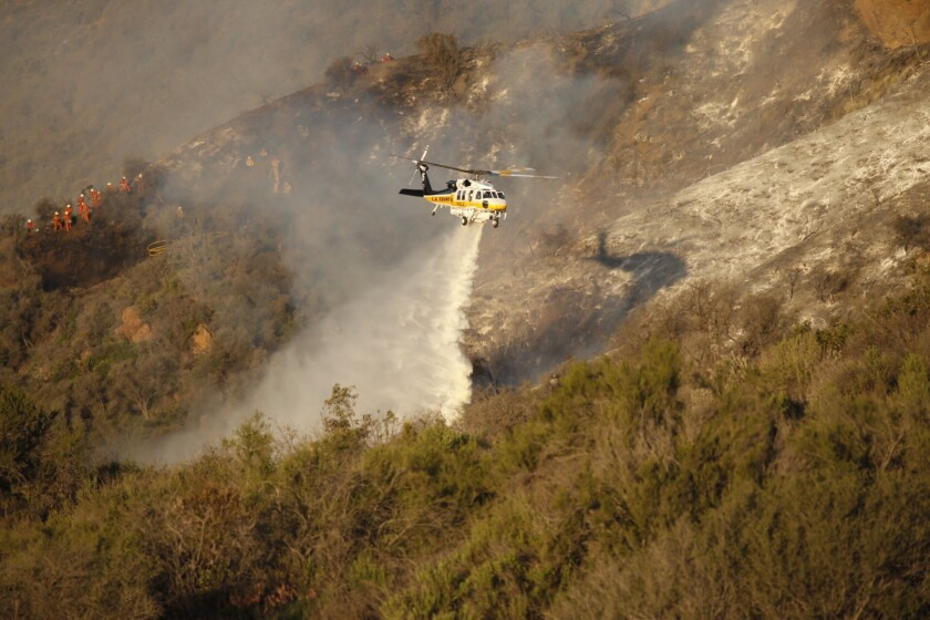 A firefighting helicopter makes a water drop on a brush fire in Malibu, where a fire crew inmate battling the blaze suffered fatal injuries Thursday.