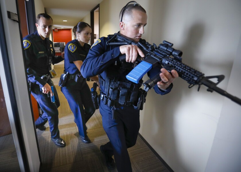 With weapons drawn during an active-shooter drill, San Diego police Officers Zacgary Zasueta, left, Ariel Oriarte, center, and Joshua Cummings, right, search for the shooter on the 14th floor of the Emerald Plaza office building Saturday in downtown San Diego.