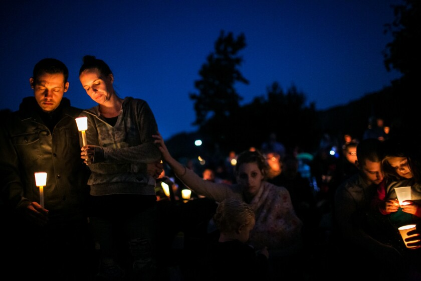Residents mourn shooting victims at a vigil in Riverbend Park in Winston, Ore.