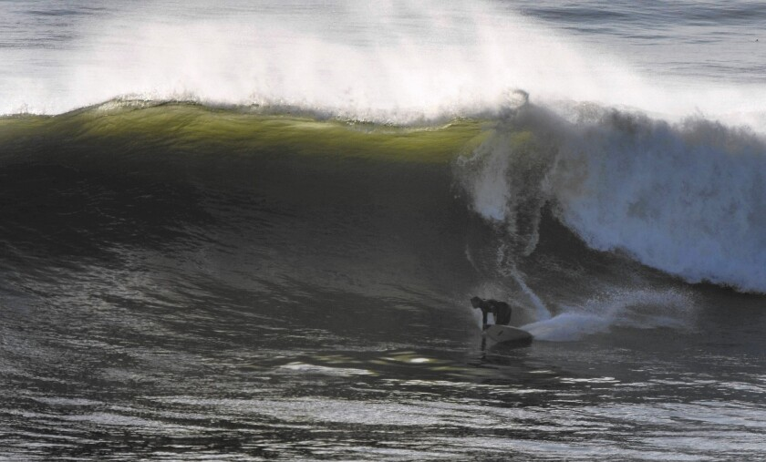 A surfer rides a big wave at Lunada Bay, where a local group called the Bay Boys keeps away outsiders.