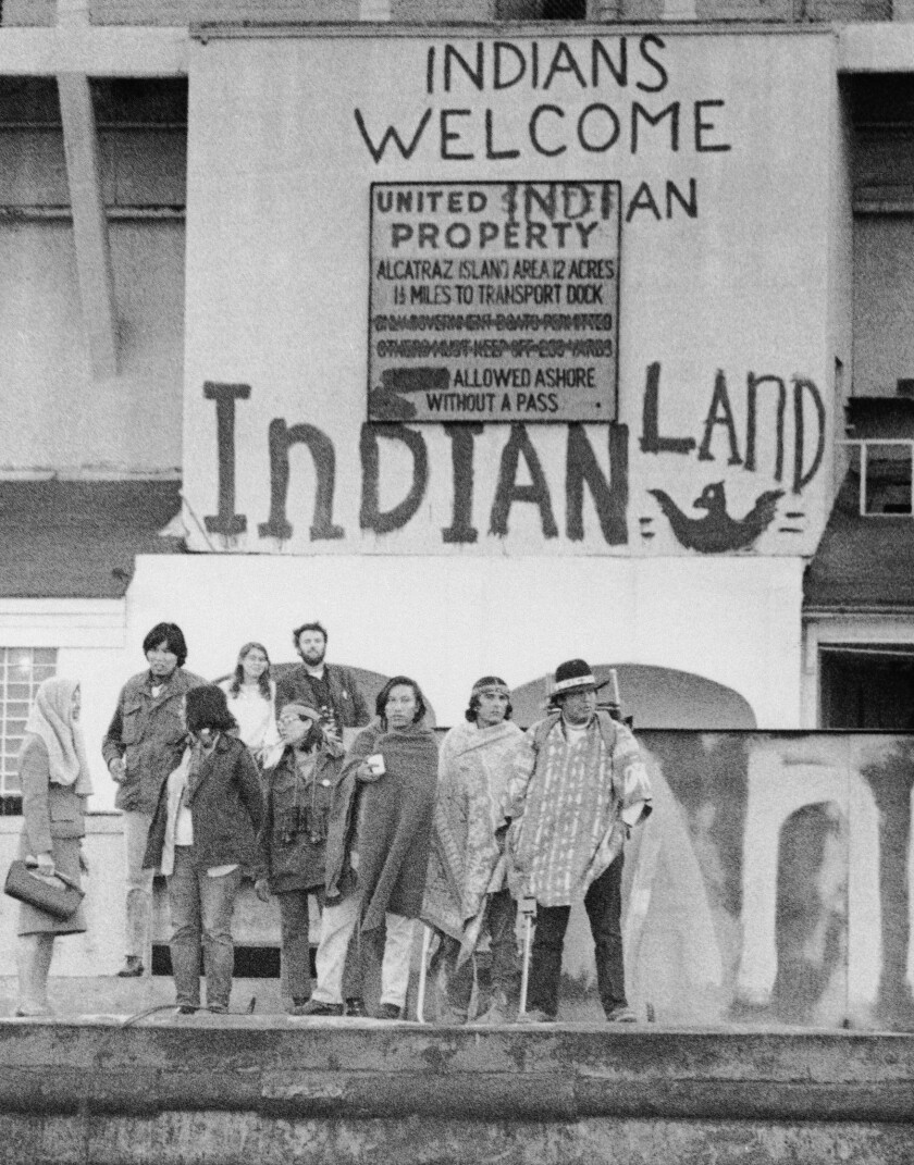 An assortment of Native Americans, part of the 200 who occupied the former prison island of Alcatraz in San Francisco, stand under signs painted at dockside, Nov. 25, 1969.