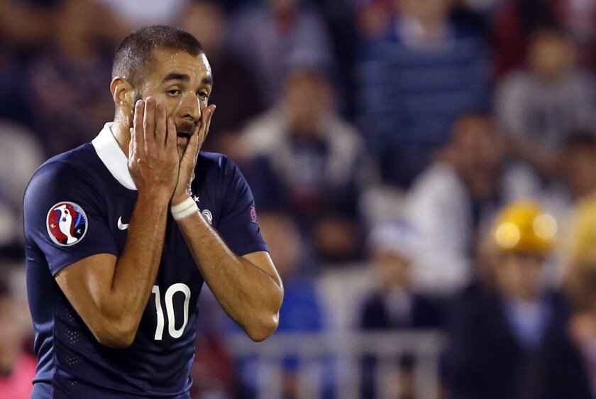 FILE - In this Sept.7, 2014 file photo, France's Karim Benzema reacts during his international friendly soccer match against Serbia, in Belgrade, Serbia. Benzema has been charged Thursday Nov.5, 2015 with conspiracy to blackmail and participating in a criminal group as part of an investigation over