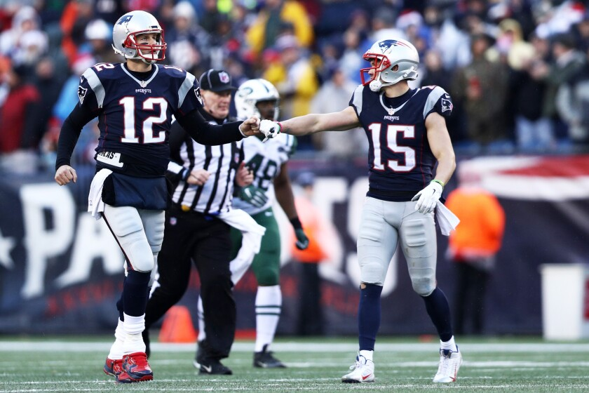 Patriots quarterbackTom Brady (12) reacts with receivers Chris Hogan (15) during the first half of a game against the New York Jetson Dec. 24.