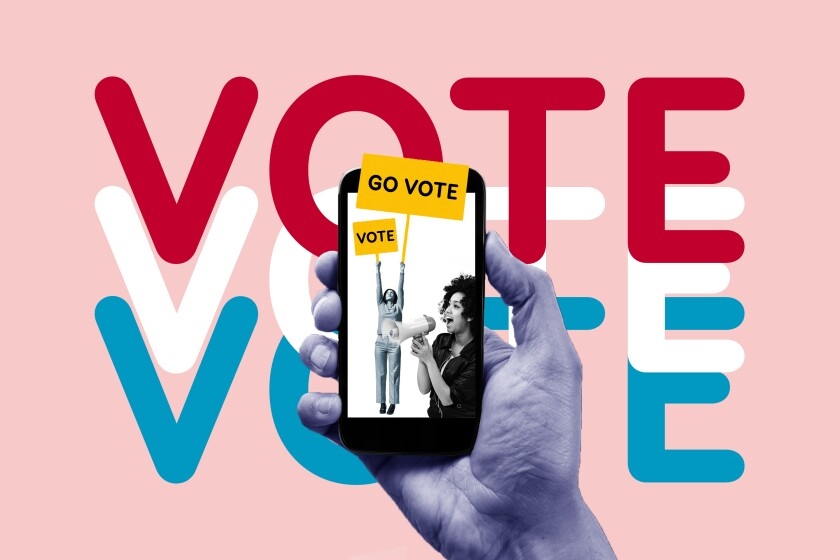 A hand holds a phone showing a picture of a woman with a sign that says Go Vote and another woman shouting into a megaphone.