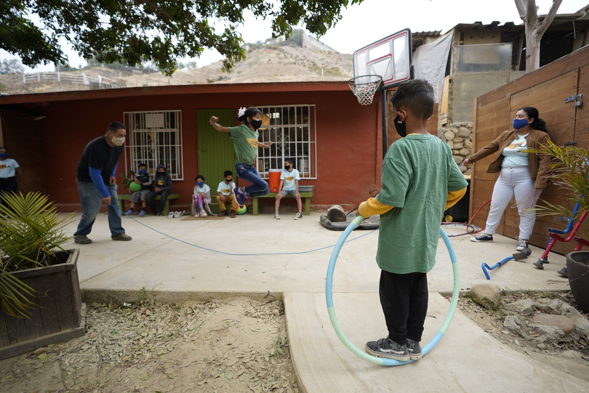 A girl jumps over a rope while a boy holding a hula hoop watches
