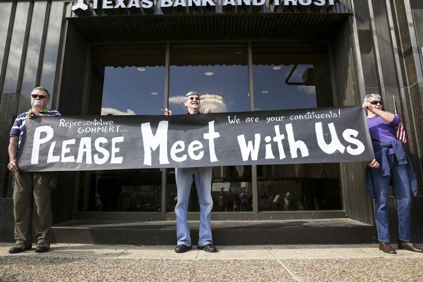 Jaime Serrano, Roy Garza and Norma Krueger hold up a sign outside during a protest against U.S. Rep. Louie Gohmert in Tyler, Texas, on Tuesday, Feb. 21, 2017. Protesters gathered outside of Jack Ryan's while Gohmert was speaking in the restaurant.