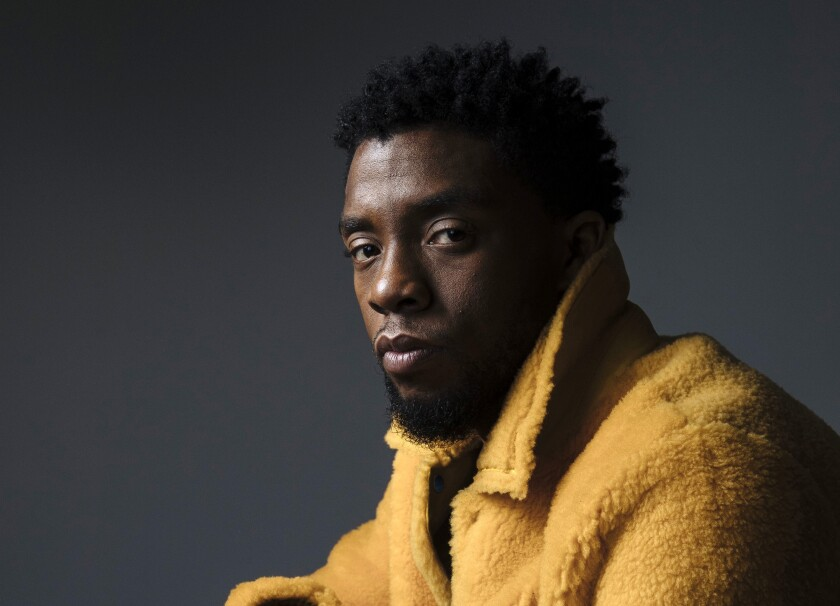 Actor Chadwick Boseman, wearing a fuzzy yellow coat and turned slightly to the side, looking at the camera