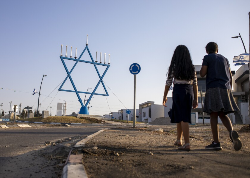 Girls walk in a new neighborhood that is under construction in Sderot, Israel