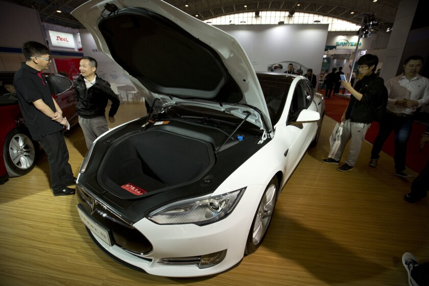 Visitors gather around a Tesla Model S electric car on display at the Beijing International Automotive Exhibition in Beijing.