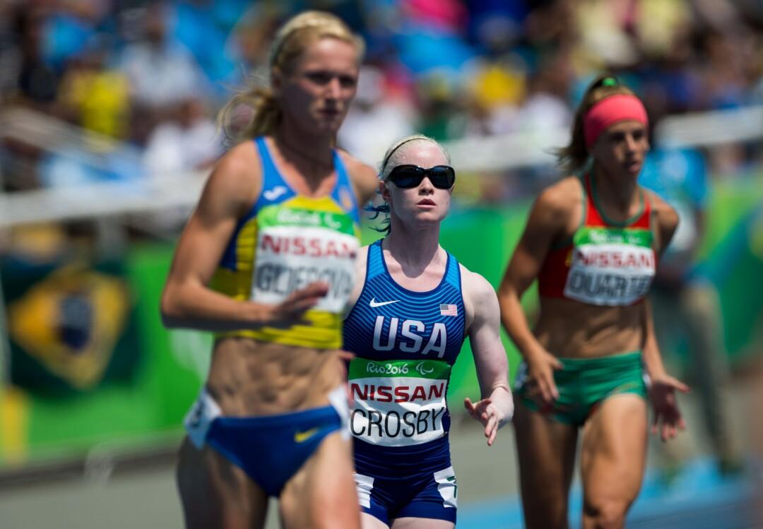 La coureuse américaine Kym Crosby court entre deux autres athlètes aux Jeux paralympiques de 2016 à Rio de Janeiro, au Brésil.