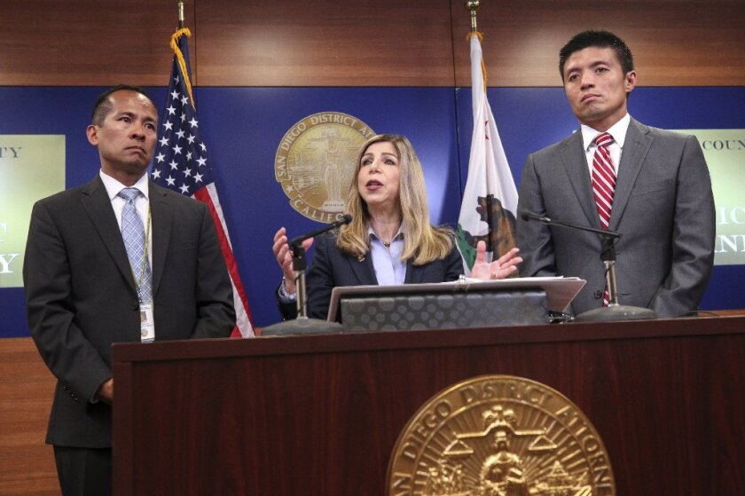 San Diego County District Attorney Summer Stephan speaks at a news conference announcing charges, including a hate crime allegation, against accused Poway synagogue shooter John T. Earnest. Deputy District Attorney Leonard Trinh (right) is the lead hate crimes prosecutor for the office and is prosecuting the case against Earnest. Deputy District Attorney David Grapilon is on the right.
