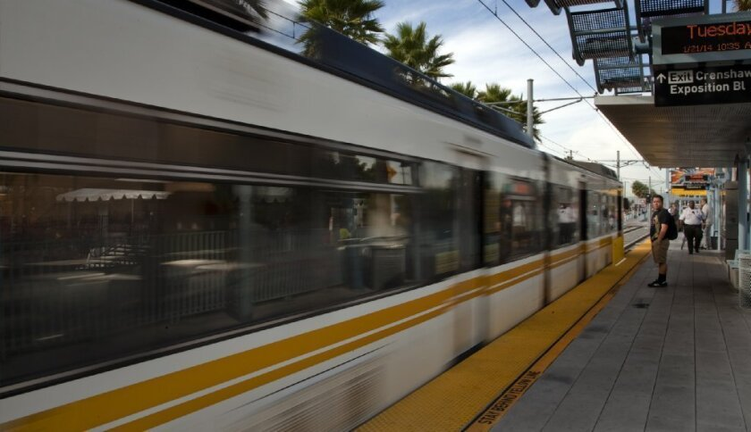 A Metro train passes by the groundbreaking ceremony Tuesday for the new Crenshaw/LAX line at the Expo/Crenshaw stop. The new line will connect the Expo and Green lines.