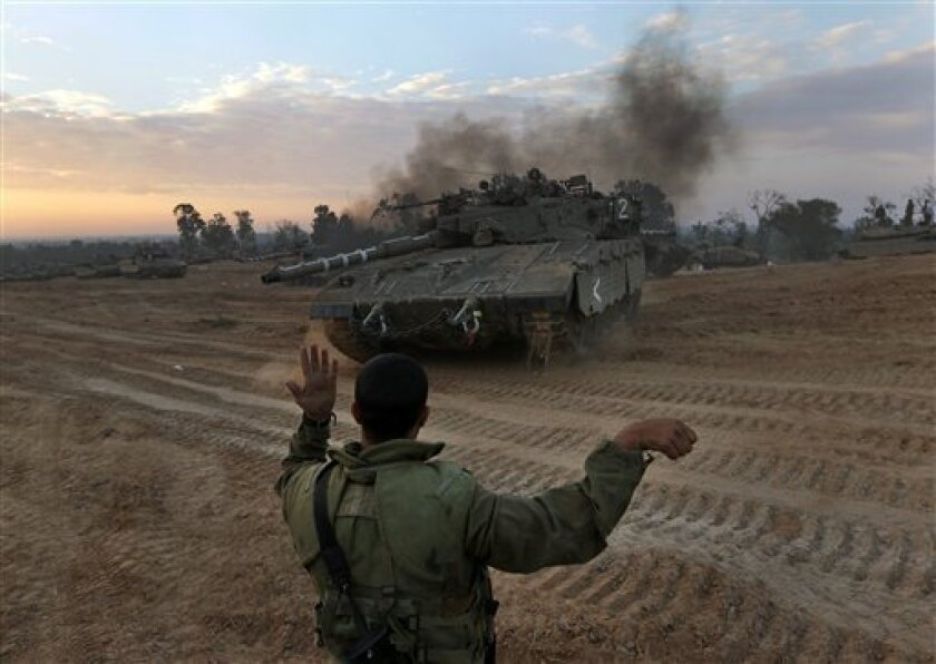 An Israeli soldier guides a tank to a new position at a staging area near the Israel Gaza Strip Border, southern Israel, Thursday, Nov. 22, 2012. A cease-fire agreement between Israel and the Gaza Strip's Hamas rulers took effect Wednesday night, bringing an end to eight days of the fiercest fighti
