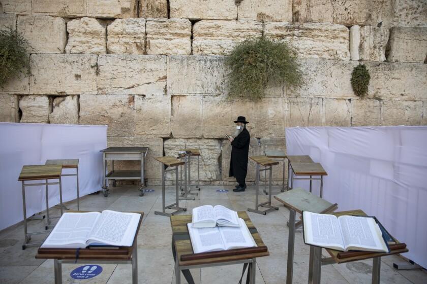 Un judío ultraortodoxo porta mascarilla mientras realiza oraciones antes del Yom Kipur