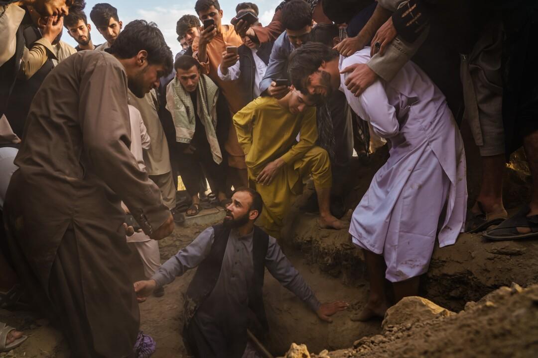 Relatives weep as they bury Nasser Ahmadi, 25