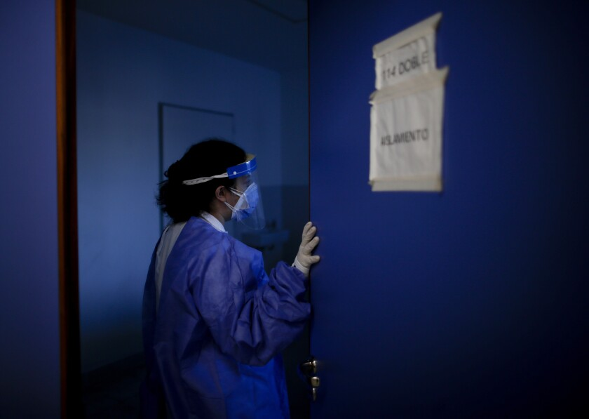 Dr. Veronica Verdino enters in a room to check on COVID-19 patients at Llavallol Dr. Norberto Raúl Piacentini Hospital in Lomas de Zamora, Argentina, Saturday, May 8, 2021. A little over a year ago, before the pandemic hit Argentina, the 31-year-old doctor did not imagine that she would be performing so many intubations. (AP Photo/Natacha Pisarenko)