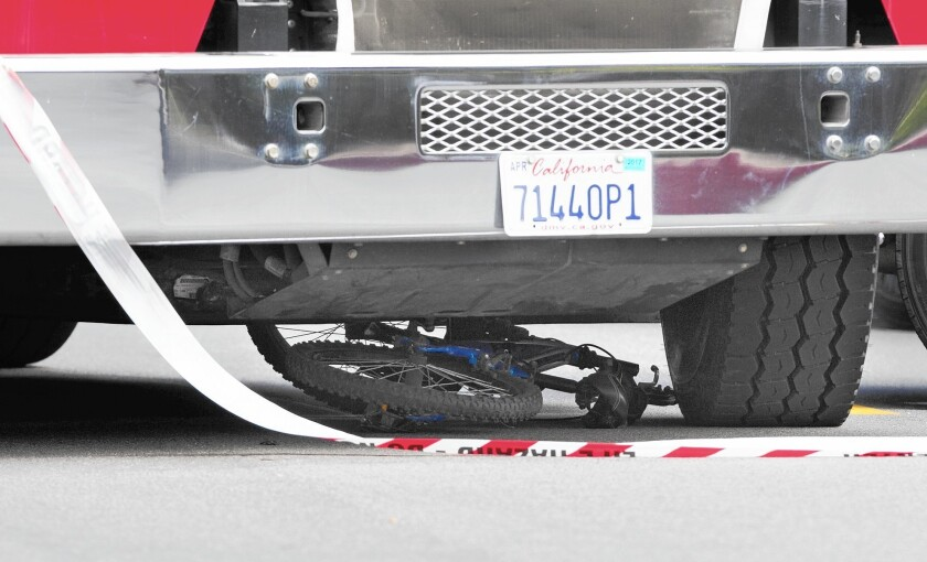 Bike lies underneath trash truck