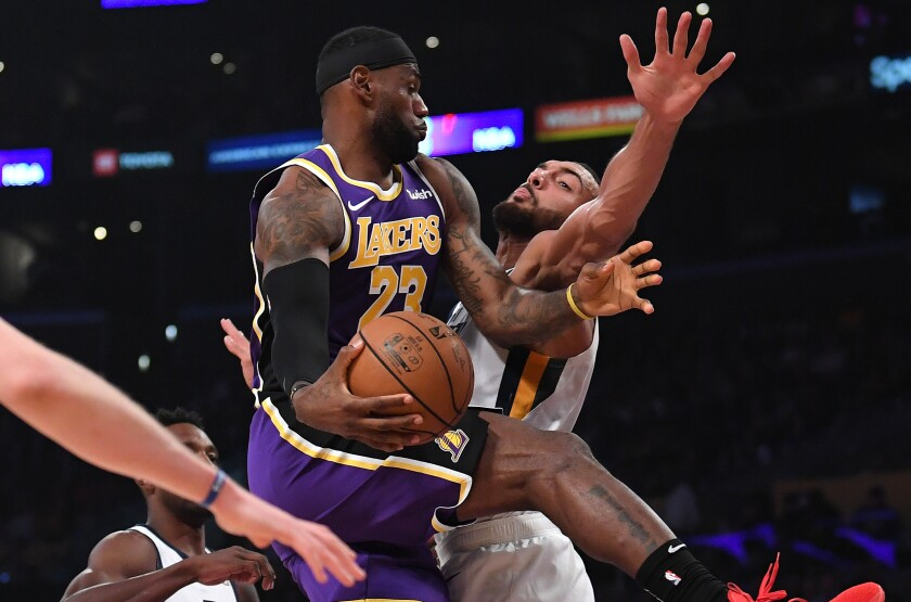 Lakers star LeBron James passes around Utah Jazz center Rudy Gobert during the first half of the Lakers' win Friday.