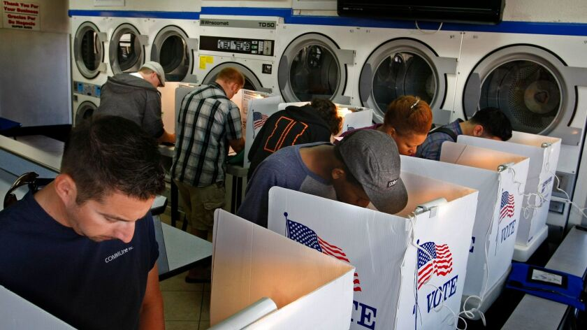Voters huddle in the dryer section to mark their ballots at Super Suds laundromat polling place on Alamitos Avenue in Long Beach on Nov 6, 2012.