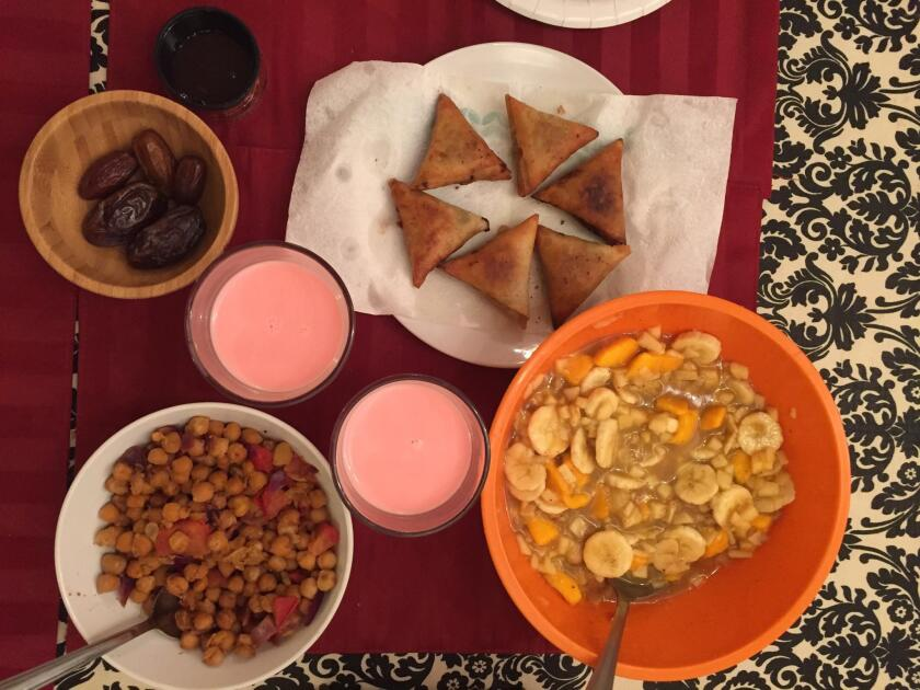 An iftar meal: Dates to start, fruit chaat, samosas, cholay, and sharbat -- a rose-flavored syrup mixed with milk.