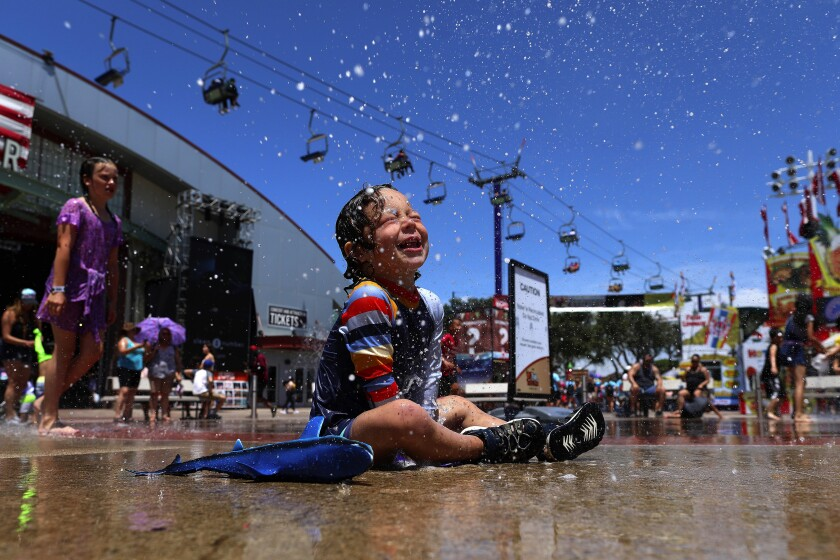 Mason Rose, 2, tries to beat the heat at the Orange County Fair in Costa Mesa, which runs through Aug. 11. Temperatures are expected to dip slightly into the weekend but will remain higher than average.