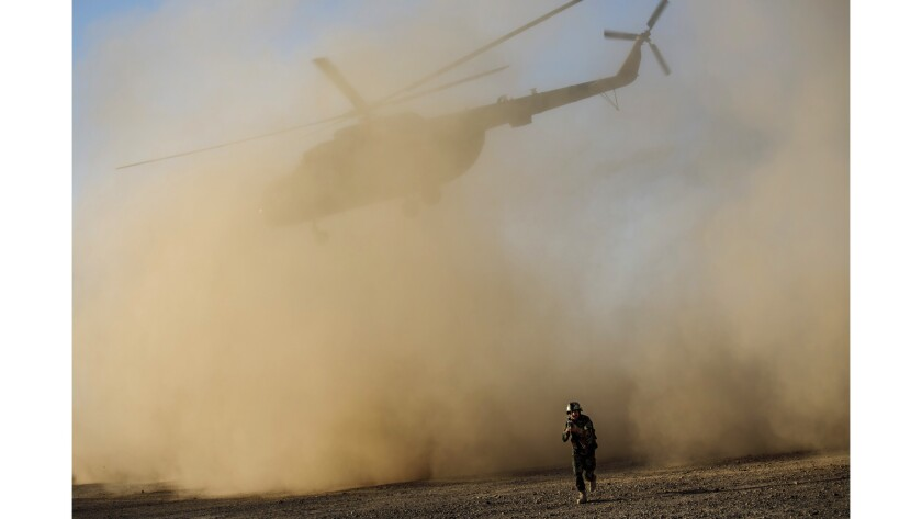 A soldier with the Afghan army leaves the landing site as an Afghan Mi-17 takes off during training near Camp Shorab, in Helmand Province.