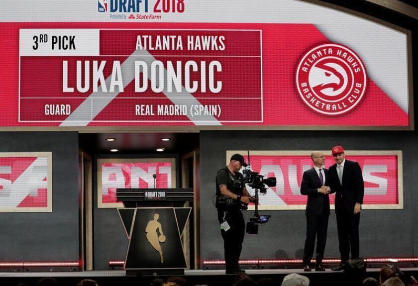 El comisionado de la NBA, Adam Silver (c) se da la mano con Luka Doncic (d), elegido número tres por los Atlanta Hawks en la noche del draft. EFE/Archivo