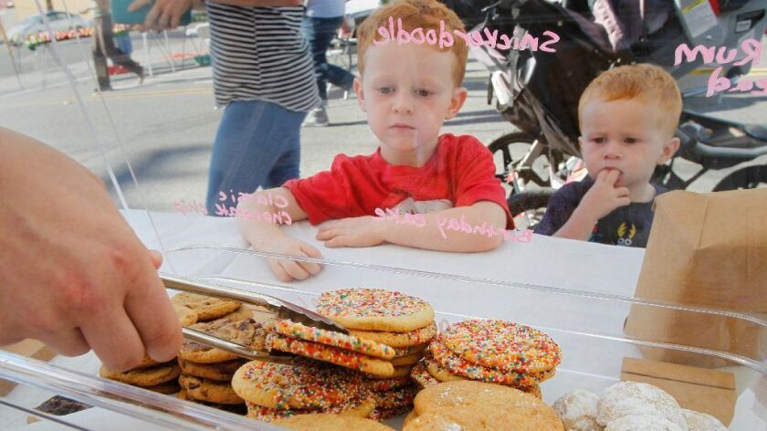 Noah Dean, left, and his brother Murphy, 2, check out the cookies at Maya's Cookies at the North Park Thursday Market.