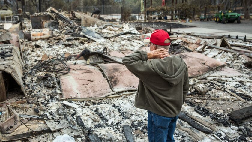 Jay Albertson takes a moment as he views his burned down home of 30 years after it was destroyed by