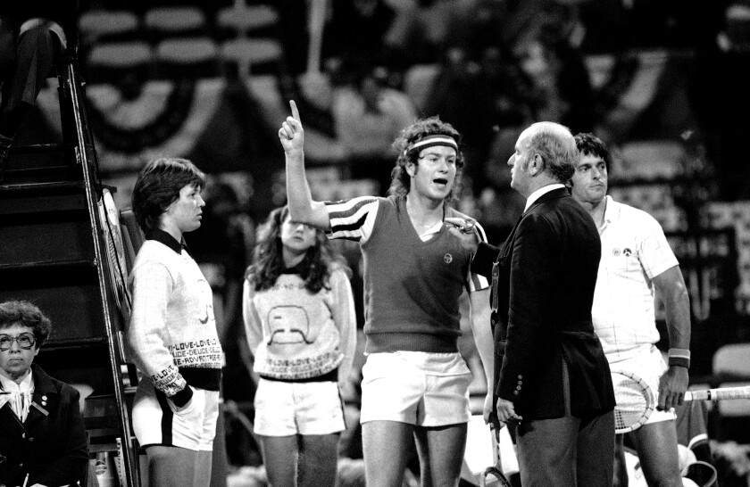 In a May 9, 1980, photo, John McEnroe points to the sky as he argues a call with an umpire and the head referee.