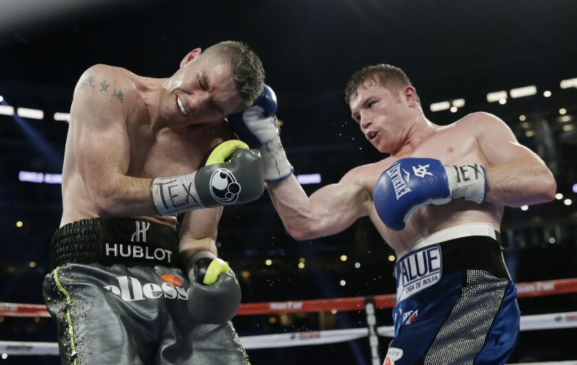 Canelo Alvarez, right, lands a right against Liam Smith during the ninth round of their fight on Sept. 17 at AT&T Stadium in Arlington, Texas.