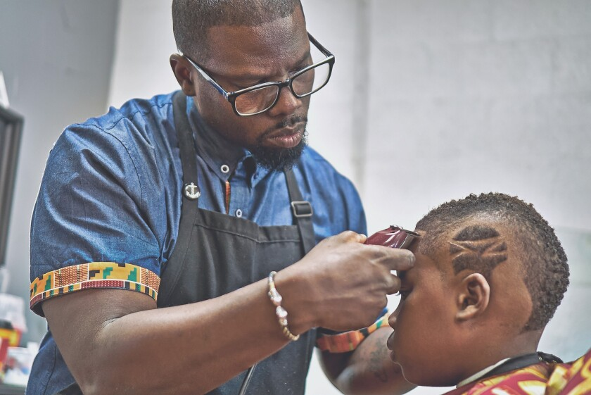 Kahlil Bryant, 41, does a fade haircut with design at his K-Cutz Barber Shop in San Diego, before he was forced to close the shop March 17 due to COVID-19 social distancing rules.