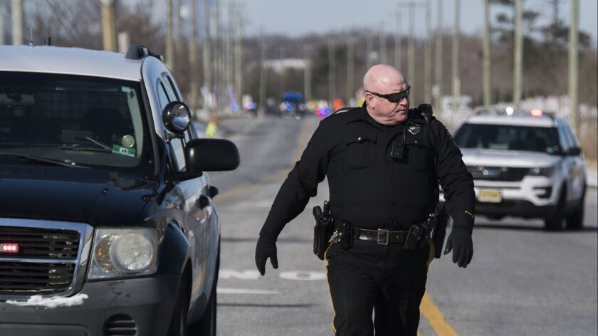 Officials respond to a hostage-taking at a UPS facility Monday, in Logan Township, N.J.