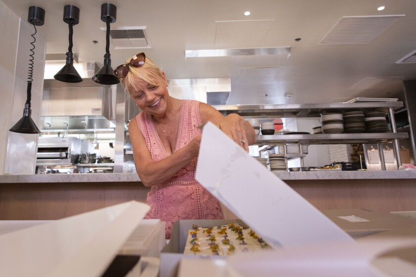 Sherry Yard peeks inside a box of cakes, made for a Gather for Good bake sale