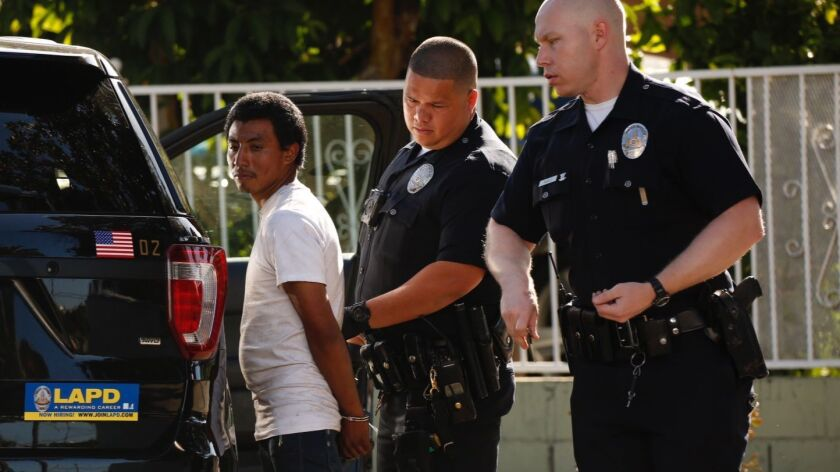 Police detain a suspect near the 400 block of Heliotrope Drive in East Hollywood on Monday morning.