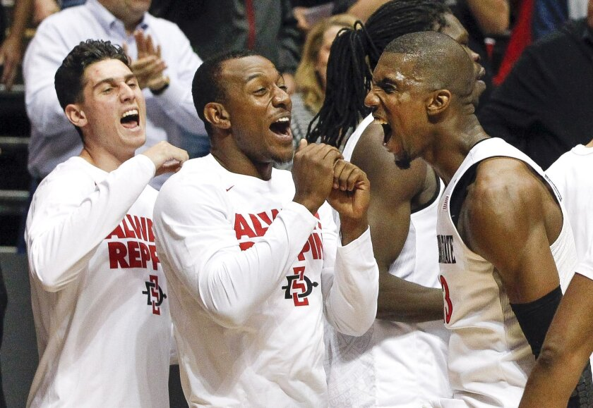 The Aztecs' Winston Shepard, right, D'Erryl Williams, center, and Ben Perez, celebrate after the Aztecs beat Georgia Tech 72-56 in the NIT quarterfinal game at the Viejas Arena in San Diego on Wednesday.