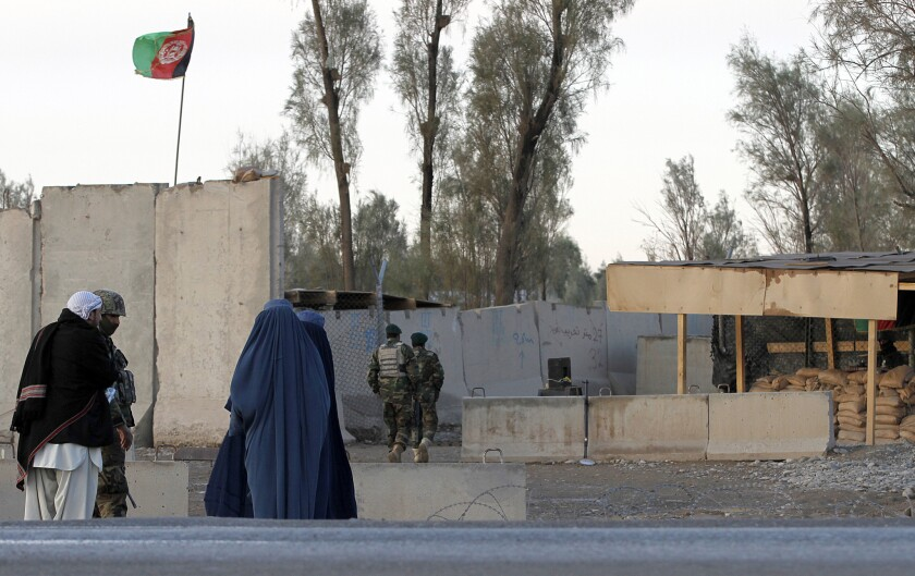 Civilians wait as Afghan security forces guard at the main gate of Kandahar airport during a clash between Taliban fighters and Afghan forces Dec. 9.