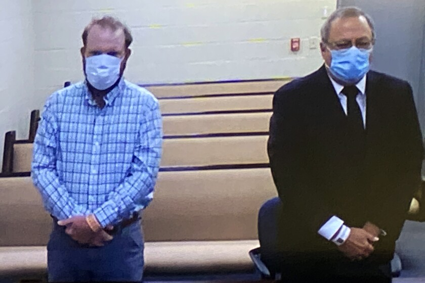 """FILE - In this image made from video, Travis McMichael, left, and Greg McMichael listen to a preliminary hearing via a court video feed, Thursday, June 4, 2020, while inside the in the Glynn County jail, in Brunswick, Ga. Defense attorneys for the men charged in the slaying of Ahmaud Arbery are asking a Georgia judge to keep reporters out of the courtroom when lawyers question potential jurors to determine if they have biases in the widely publicized case. In their court motion, defense attorneys say it's critical that potential jurors feel as comfortable as possible answering questions about race and other sensitive topics to ensure the McMichaels are tried by an impartial jury. """"We must create the best environment for jurors to share their true thoughts, beliefs, biases, and prejudices about very sensitive subjects,"""" Jason Sheffield, an attorney for Travis McMichael, said in an email Thursday, July 15, 2021. (Glynn County Jail via AP, Pool)"""